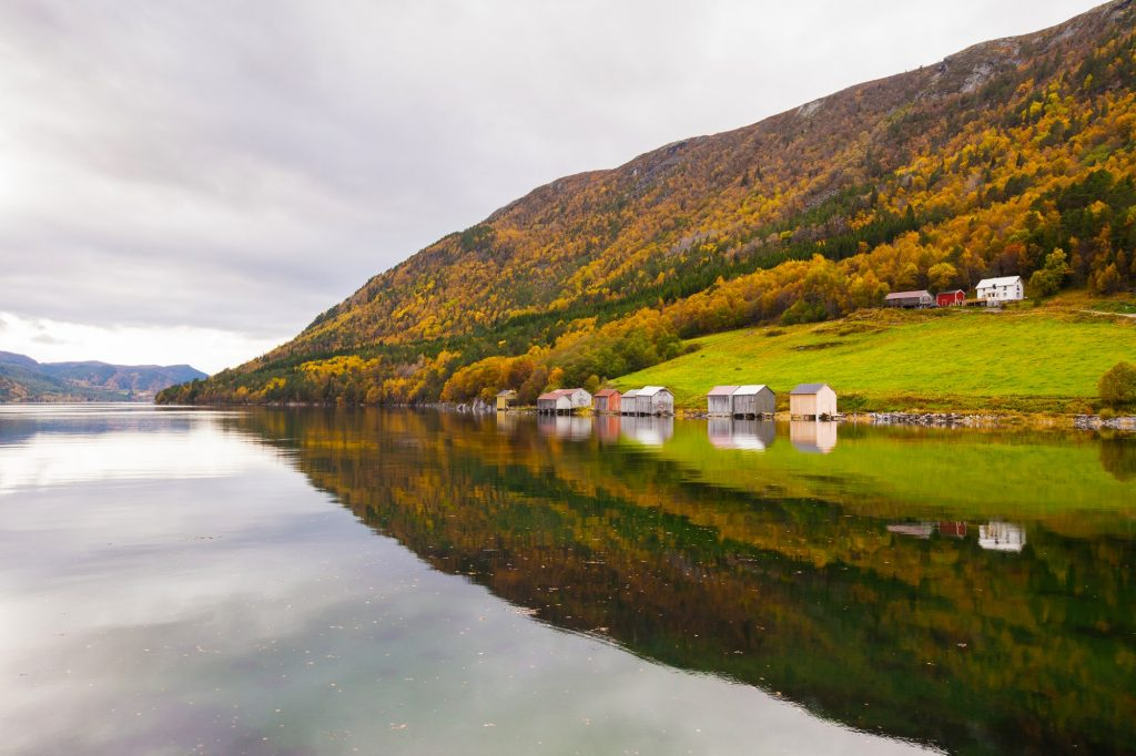 autumn rural landscape with houses near river, Norway
